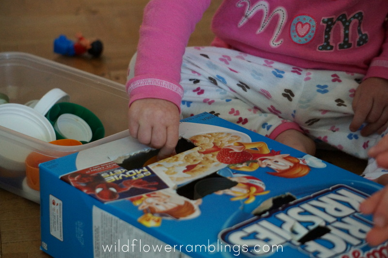 bottle tops and cardboard box - 21 Activities for One Year Olds - Baby Play - Wildflower Ramblings